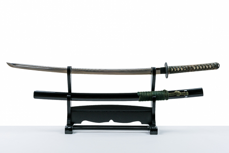 Japanese iaido sword in black wooden stand and white background. Still life studio shot of Japanese sword.