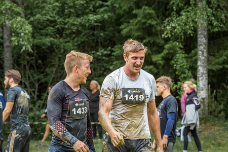 exhausting: Stockholm, Sweden - June 03, 2017: Close up front view, two dirty caucasian male athletes talking after completing a mud obstacle at the annual event Toughest Stockholm. A few people in the background.