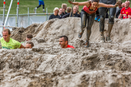 Stockholm, Sweden - June 03, 2017: Front view, group of caucasian men an women in a mud obstacle struggling to complete the course of the annual event Toughest Stockholm.