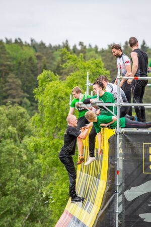 Stockholm, Sweden - June 03, 2017: Side view with group of young people climbing and standing on an obstacle wall, trying to complete the annual obstacle course event Toughest Stockholm.