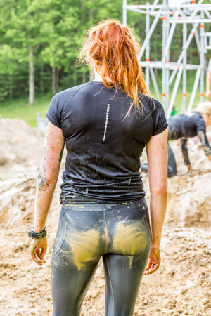 Stockholm, Sweden - June 03, 2017: Close up back view,  one caucasian woman with dirty muddy outfit looking at a mud bostacle after completing the course of the annual event Toughest Stockholm. People in the background.