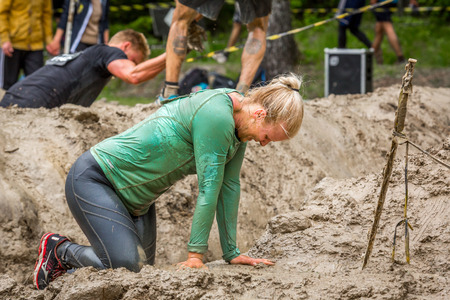 exhausting: Stockholm, Sweden - June 03, 2017: Close up side view, one exhausted caucasian woman in a mud obstacle to complete the course of the annual event Toughest Stockholm. People in the background. Editorial