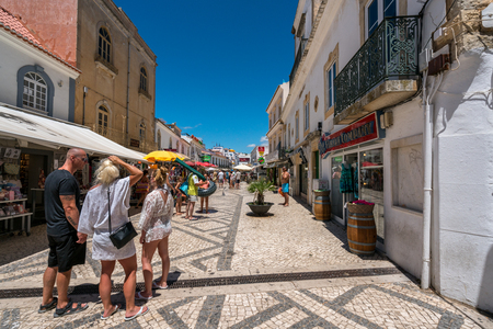 People on shopping street. Albufeira, Portugal - July 19, 2017: Perspective street view of the old parts av Albufeira city with tourists shopping and some about to go to the beach. Many shops and restaurants along the street. Editorial