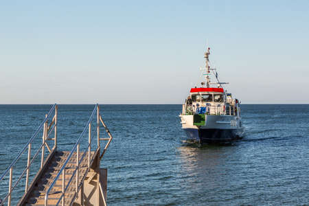 Ship approaching shore. Gotska sandon, Sweden - August 2, 2017:  View from the shore of a passenger boat at the Baltic sea approaching a gangway at the island Gotska sandon to pick up tourists. Crew can be seen standing on the deck.