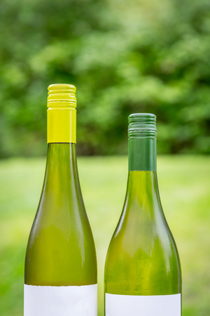 Two full green wine bottles next to each other outdoors.