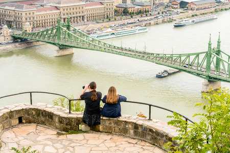 A young couple sitting at a viewpoint up high taking pictures of Liberty bridge over the Danube river, Budapest Hungary. Stock Photo - 88170028