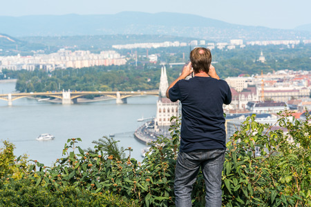 A man standing in green bushes up high at a viewpoint to take a panoramic picture Budapest below. Stock Photo - 88170016