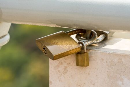 Close up of three padlocks attached to a steel railing on white marble and green background. Stock Photo - 88170019