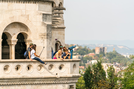 Budapest, Hungary - September 27, 2017: Selective focus side view of a group of young caucasian male and female tourists standing at a viewpoint outside and below Matthias Church in Budapest Hungary to take selfies and pictures of the city of Budapest bel Editorial