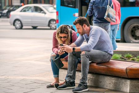 Budapest, Hungary - September 25, 2017: Close up shot of a casual young caucasian couple resting on a wooden bench in Budapest Hungary to look at their mobile phones. Incidental people and traffic in the background. Stock Photo - 87197844