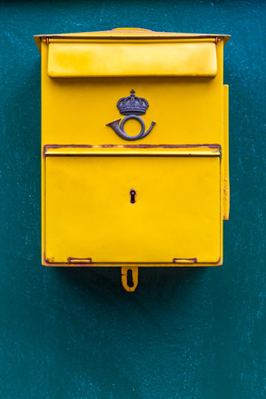 Close up of a classic yellow public postal mail box with a mail symbol, mounted on a blue wall outdoors. Stock Photo - 88491524