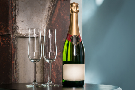 Indoors still life shot of a unopened champagne bottle and two empty glasses on a table. Label with copy space. Stock Photo - 88491527