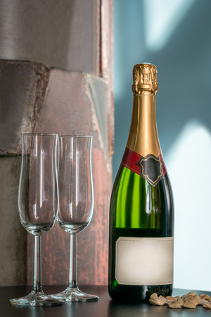 Still life shot of a unopened champagne bottle and two empty glasses on a table with snacks. Label with copy space. Stock Photo