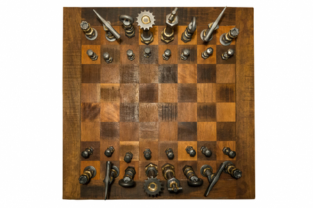Unusual wooden chess board with forged iron pieces seen from above, isolated on white. Stock Photo - 88491530