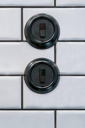Two round black decorative bakelite light switches on white tile wall.