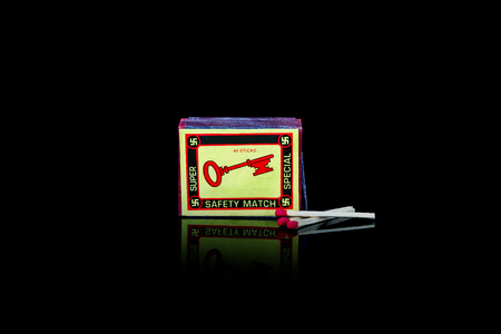 A vintage match box with a key  on the front. Isolated studio shot on black background.