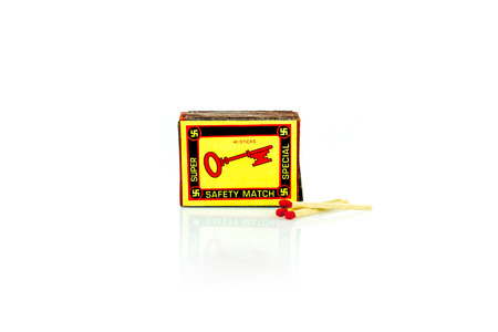A vintage match box with a key  on the front. Isolated studio shot on white background.