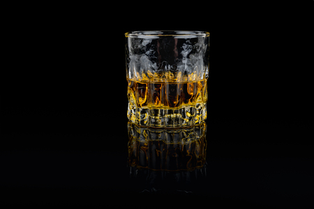 Beautiful golden tasty whiskey in a classic whiskey glass. Isolated studio shot on black background. Stock Photo - 90458032