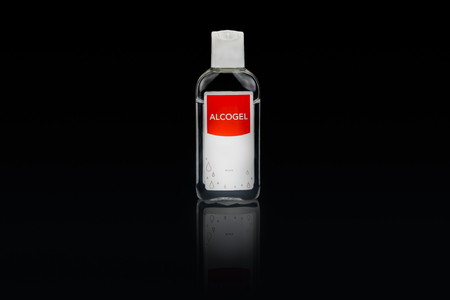 Isolated alcogel hand disinfectant in a small plastic bottle with red label, studio shot on black background.