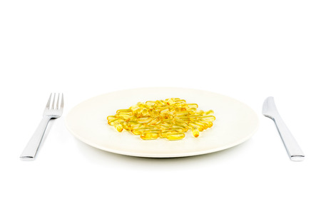 Selective focus of soft yellow capsules with healthy omega 3 fish oil on a dinner plate with knife and fork. Stock Photo - 90811526