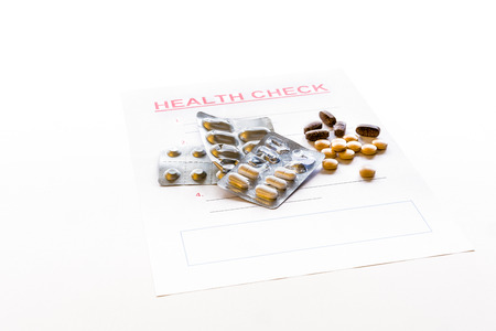 A blank health check form with medicine, vitamins, pills and packaging scattered on it. Stock Photo - 90910009