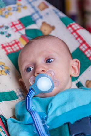 Infant boy with a pacifier lying down and looking to the side. Stock Photo