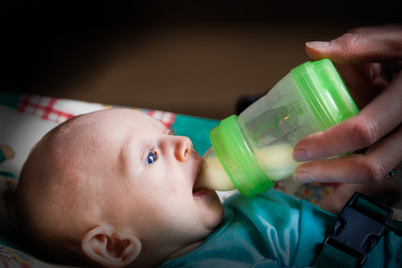 Shallow depth of field of infant boy fed with a feeding-bottle. Dark profile view.