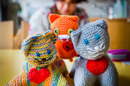 Shallow depth of field of three  knitted stuffed toy cats with red hearts, woman sitting in the background. Stock Photo