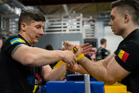 STOCKHOLM, SWEDEN - JANUARY 13, 2018: Profile view of a Swedish and Romanian male arm wrestler in a match at the event Arm Battle of Sweden outside of Stockholm January 13, 2018. Editorial