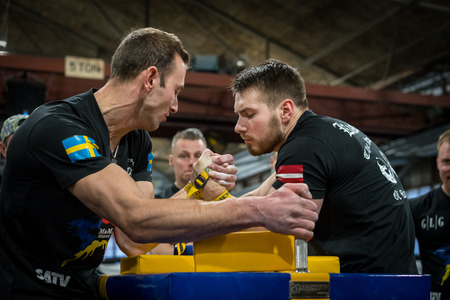 STOCKHOLM, SWEDEN - JANUARY 13, 2018: Profile view of a Swedish and Latvian male arm wrestler in a match at the event Arm Battle of Sweden outside of Stockholm January 13, 2018. Editorial