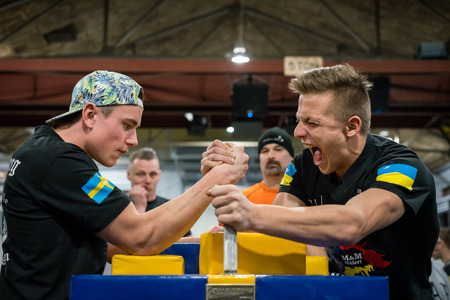 STOCKHOLM, SWEDEN - JANUARY 13, 2018: Profile view of a Swedish and Ukrainian male arm wrestler in a match at the event Arm Battle of Sweden outside of Stockholm January 13, 2018. Editorial