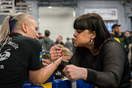 STOCKHOLM, SWEDEN - JANUARY 13, 2018: Profile view of two Swedish female arm wrestlers in a friendly match at the event Arm Battle of Sweden outside of Stockholm January 13, 2018.