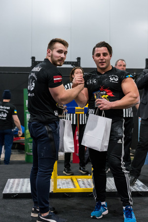 STOCKHOLM, SWEDEN - JANUARY 13, 2018: A swedish and Latvian male armwrestler getting a price at the award ceremony during the event Arm Battle of Sweden outside of Stockholm January 13, 2018.
