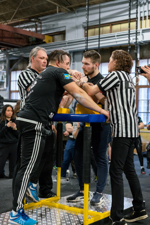 STOCKHOLM, SWEDEN - JANUARY 13, 2018: Two referees adjusting the hands on a Swedish and Latvian male armwrestler at the event Arm Battle of Sweden outside of Stockholm January 13, 2018.