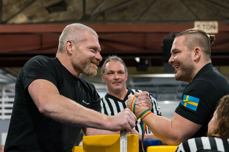 STOCKHOLM, SWEDEN - JANUARY 13, 2018: Profile view of two Swedish male arm wrestlers and a referee in a match at the event Arm Battle of Sweden outside of Stockholm January 13, 2018. Editorial
