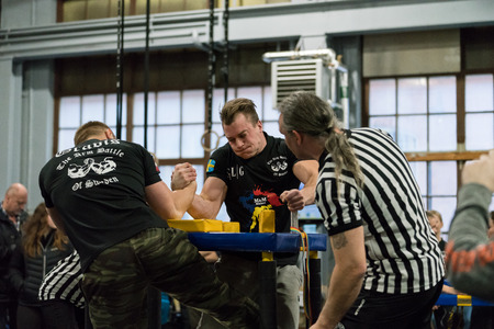 STOCKHOLM, SWEDEN - JANUARY 13, 2018: A Swedish and Latvian male arm wrestler and referrees in a match at the event Arm Battle of Sweden outside of Stockholm January 13, 2018, spectators in the background.