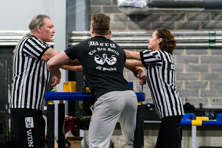 STOCKHOLM, SWEDEN - JANUARY 13, 2018: Two referees adjusting the hands on a Swedish male armwrestler at the event Arm Battle of Sweden outside of Stockholm January 13, 2018.