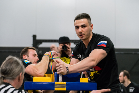 STOCKHOLM, SWEDEN - JANUARY 13, 2018: Profile view of a Swedish and Russian male arm wrestler and a referee in a match at the event Arm Battle of Sweden outside of Stockholm January 13, 2018.