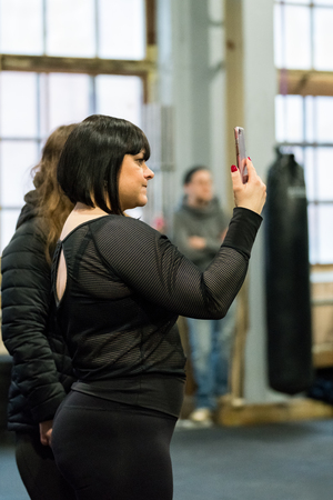STOCKHOLM, SWEDEN - JANUARY 13, 2018: Cute fit woman in black taking a photo with a cellphone during the event Arm Battle of Sweden outside of Stockholm January 13, 2018. Stock Photo - 94169870