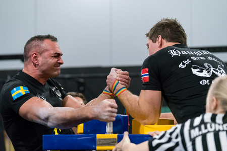 STOCKHOLM, SWEDEN - JANUARY 13, 2018: Profile view of a Swedish and Norwegian male arm wrestler and a referee in a match at the event Arm Battle of Sweden outside of Stockholm January 13, 2018. Editorial