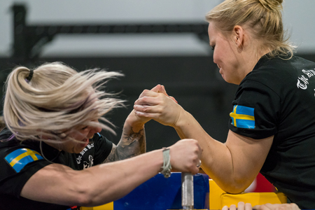 STOCKHOLM, SWEDEN - JANUARY 13, 2018: Profile view of two Swedish female arm wrestlers in a match at the event Arm Battle of Sweden outside of Stockholm January 13, 2018. Stock Photo - 94169877