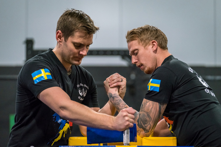 STOCKHOLM, SWEDEN - JANUARY 13, 2018: Profile view of two Swedish male arm wrestlers warming up at the event Arm Battle of Sweden outside of Stockholm January 13, 2018. Stock Photo - 94169880
