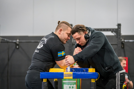 STOCKHOLM, SWEDEN - JANUARY 13, 2018: Profile view of two Swedish male arm wrestlers warming up at the event Arm Battle of Sweden outside of Stockholm January 13, 2018.