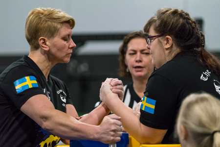 STOCKHOLM, SWEDEN - JANUARY 13, 2018: Profile view of two Swedish female arm wrestlers and one referee in a match at the event Arm Battle of Sweden outside of Stockholm January 13, 2018.