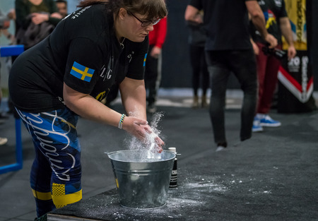 STOCKHOLM, SWEDEN - JANUARY 13, 2018: A Swedish female arm wrestler preparing with chalk at the event Arm Battle of Sweden outside of Stockholm January 13, 2018. Stock Photo - 94169884