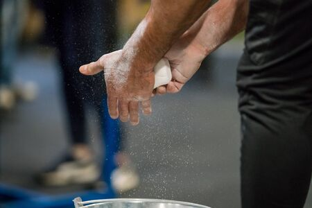 Close up selective focus of male hands preparing with chalk magnesium before exercise.