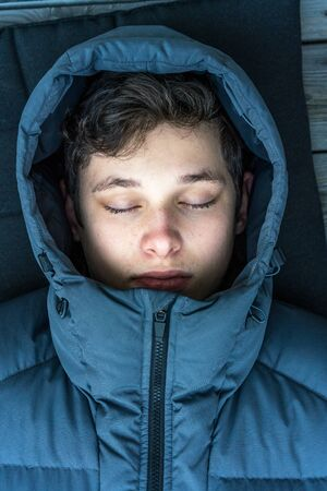 Close up portrait of young man teenager with eyes closed wearing blue winter jacket outdoors.