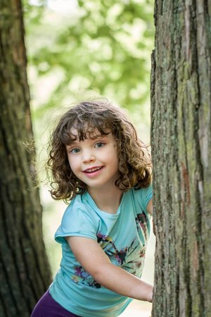 Close up summer portrait of a cute pretty smiling preschool girl with tangled hair, standing between two trees. Stock Photo - 94678287