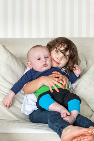 Cute portrait of sister and brother siblings holding each other on a couch. Small girl and a baby boy. Stock Photo - 94938379