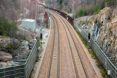 View from above of double railroad tracks in a mountain and forest evironment. Stock Photo - 94967910